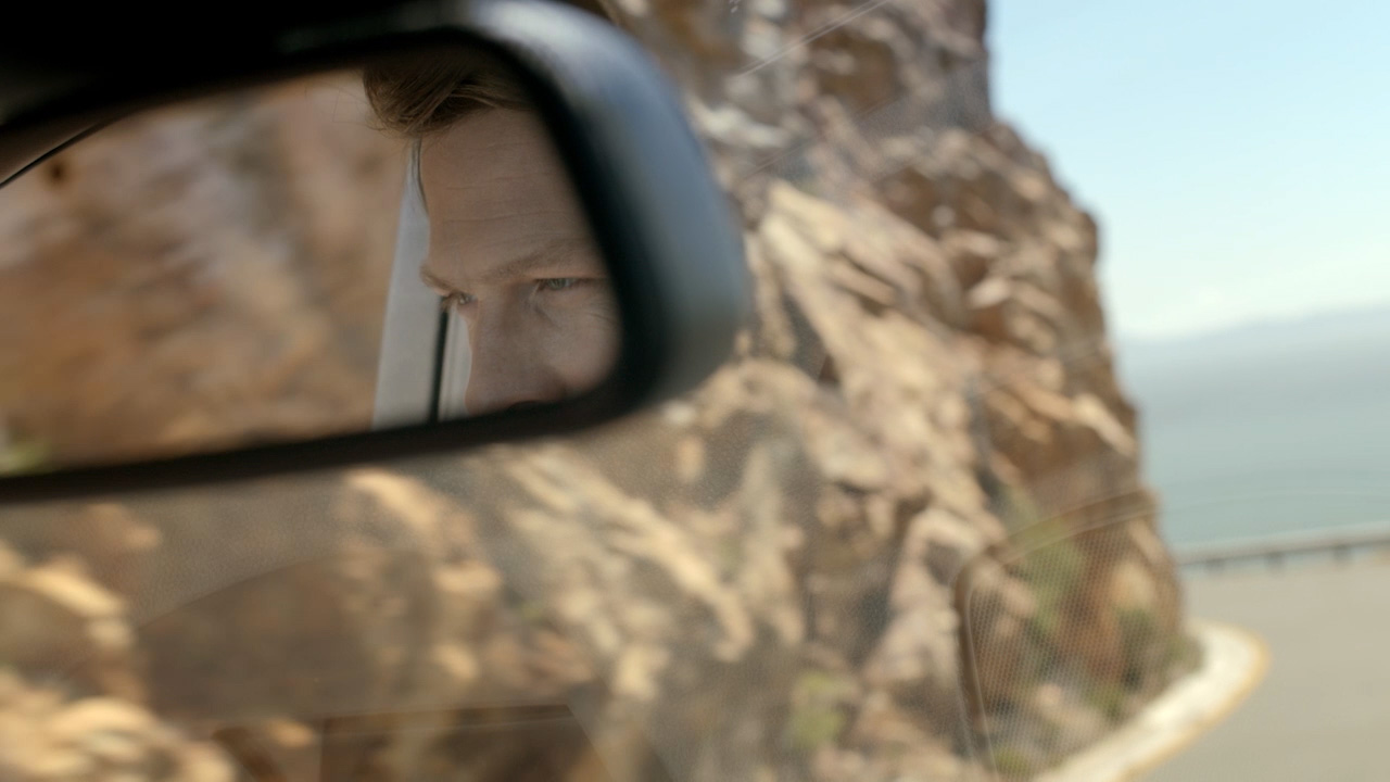 close up of eyes in rearview mirror on a coastal highway
