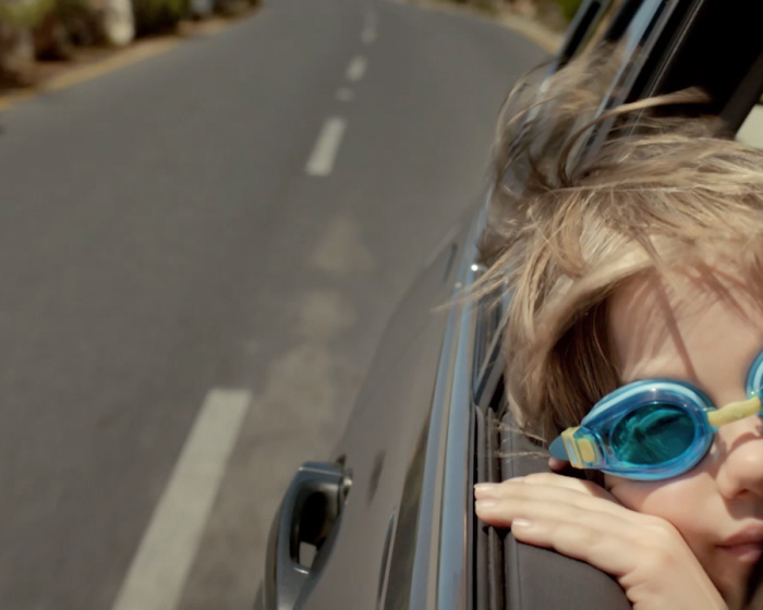 boy wearing goggles looking out car window